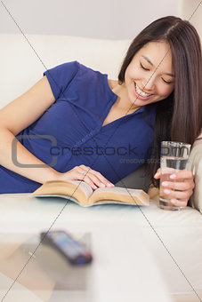 Smiling asian girl lying on the sofa reading a novel and drinking water