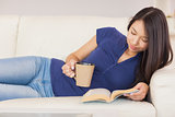 Beautiful asian girl lying on the sofa reading a novel and drinking hot beverage