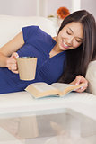 Happy asian girl lying on the sofa reading a novel and drinking hot beverage
