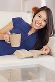 Smiling asian girl lying on the sofa reading a novel and drinking hot beverage
