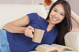 Attractive young asian woman lying on the sofa reading a novel and drinking hot beverage