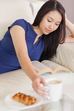 Pretty young asian woman lying on the sofa reading a book reaching for her coffee