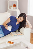 Pretty young asian woman lying on the sofa reading a book holding her coffee