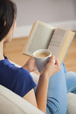 Young woman sitting on the sofa reading a book holding her coffee