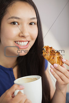 Young asian woman having a pastry with a cup of coffee