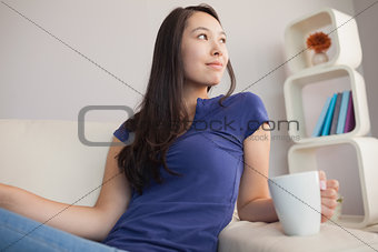 Attractive young asian woman sitting on the couch holding mug