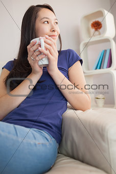 Thoughtful young asian woman sitting on the couch holding mug