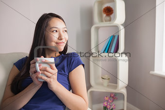 Thinking young asian woman sitting on the couch holding mug