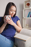 Reading asian woman sitting on the couch holding mug