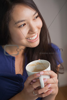 Smiling asian woman holding mug of coffee looking away