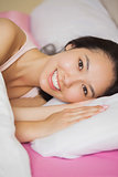 Pretty young asian woman lying in her bed smiling at the camera