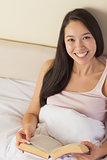 Cheerful young asian woman sitting in bed reading a book looking up at camera