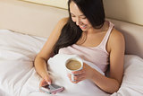 Cheerful young asian woman sitting in bed texting on her smartphone and drinking coffee