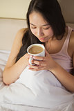 Cheerful young asian woman sitting in bed smelling her morning coffee