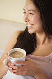 Cheerful young asian woman sitting in bed holding her morning coffee