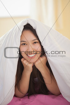 Cute young asian woman under her duvet smiling at camera