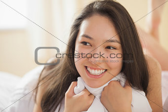 Cute young asian woman holding her duvet and smiling
