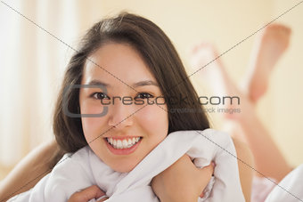 Cute young asian woman grasping her duvet and smiling