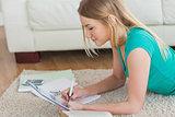 Side view of woman lying on floor working on homework