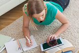 Blonde woman lying on floor using tablet to do her assignment