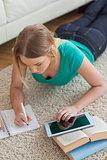 Focused young woman lying on floor using tablet to do her assignment