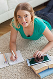 Cheerful young woman lying on floor using tablet to do her assignment