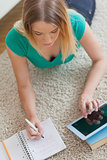 Woman lying on floor doing her homework using tablet