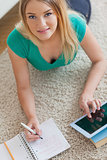 Happy woman lying on floor doing her homework using tablet
