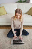Blonde woman sitting on floor using laptop