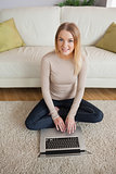 Happy woman sitting on floor using laptop