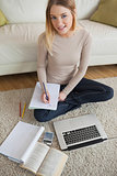 Woman doing homework and sitting on floor using laptop