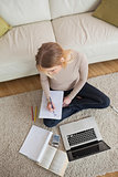 Blonde doing homework and sitting on floor using laptop