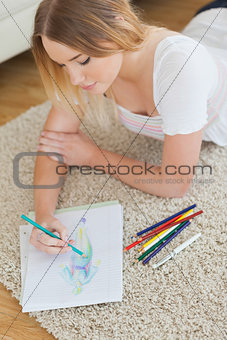 Happy young woman lying on floor sketching on paper