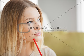 Thoughtful woman holding red pen