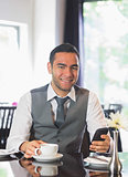 Smiling businessman having coffee and holding phone