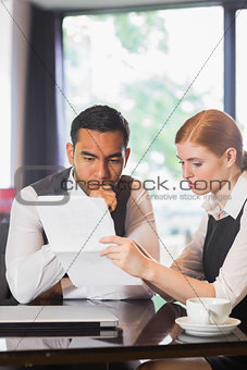 Serious business partners working together in a cafe