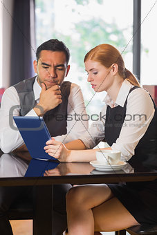 Business partners working on tablet pc together in a cafe