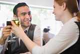 Smiling business partners clinking wine glasses