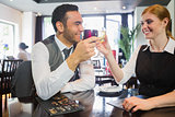 Happy business partners clinking wine glasses