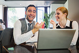Laughing business people working on laptop