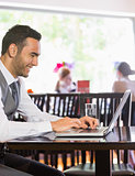 Smiling businessman looking at laptop screen