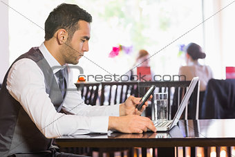 Serious businessman using phone while working on laptop
