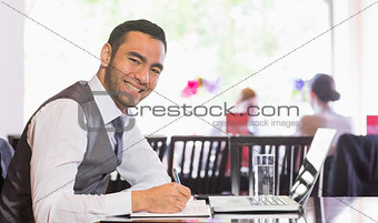Smiling businessman writing while looking at camera