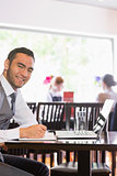 Happy businessman writing while smiling at camera
