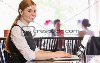 Smiling businesswoman working on laptop looking at camera