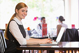 Happy businesswoman typing on laptop while smiling at camera