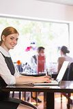 Attractive businesswoman working on laptop smiling at camera