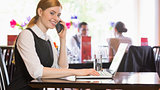Smiling businesswoman calling on phone typing on laptop and looking at camera