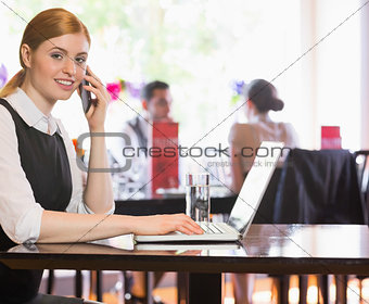 Smiling businesswoman looking at camera while calling on phone