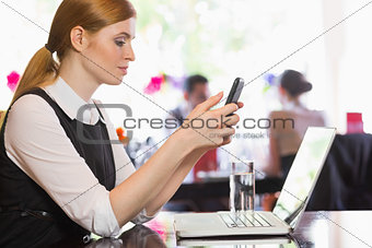 Concentrated businesswoman sending a text